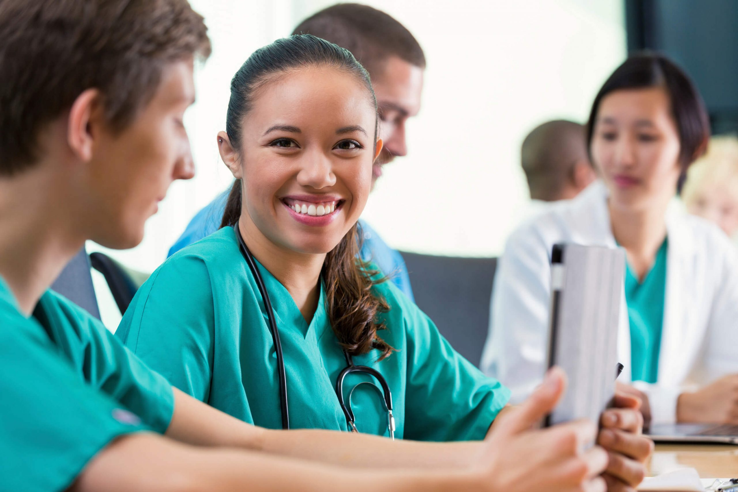 Health care professionals sitting at table with young female professional looking at you