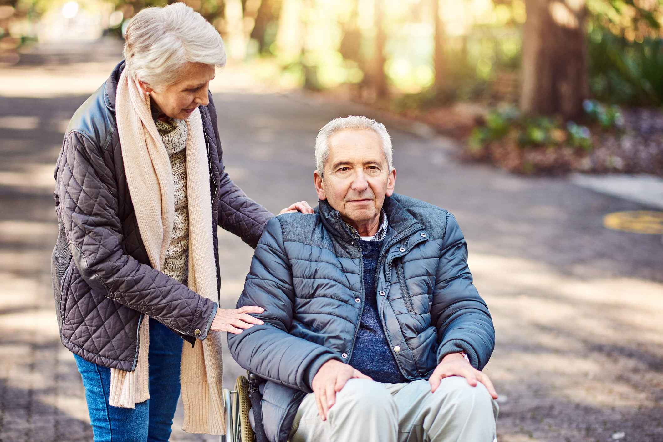 Older man sitting in wheelchair with wife standing along side him in a park.