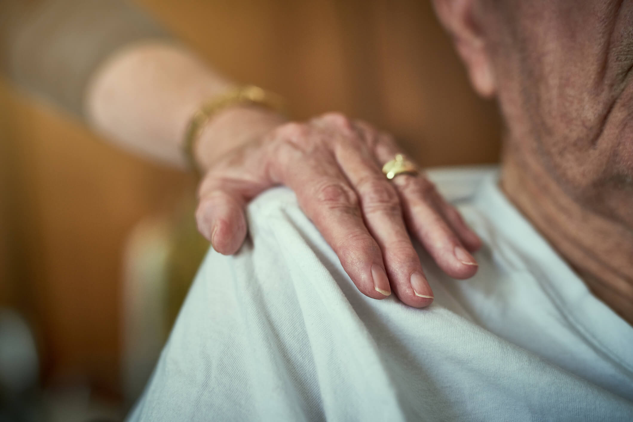 Photo of elderly woman's hand lovingly resting upon her husband's shoulder.